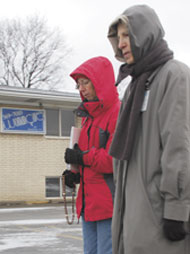 Barb Yagely and Joan Cooney, parishioners at St. Anastasia in Troy and St. Hugo of the Hills in Bloomfield Hills, respectively, pray in front of Woman Care abortion clinic.